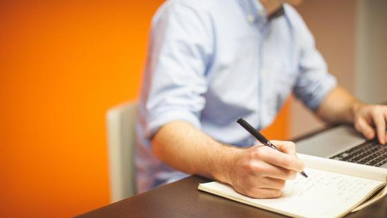 Мужчина пишет что-то в блокнот
