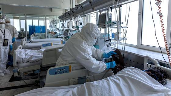 Работник больницы стоит возле реанимационной койки