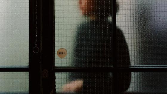 Девушка стоит за прозрачной витриной