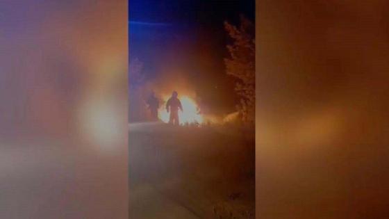 мужчины стоят у горящей машины