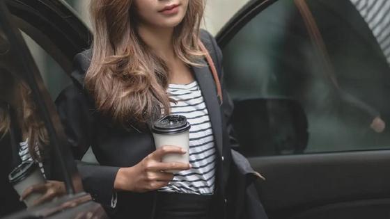 Девушка выходит из автомобиля с кофе в руке
