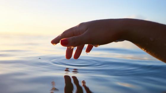 рука трогает воду