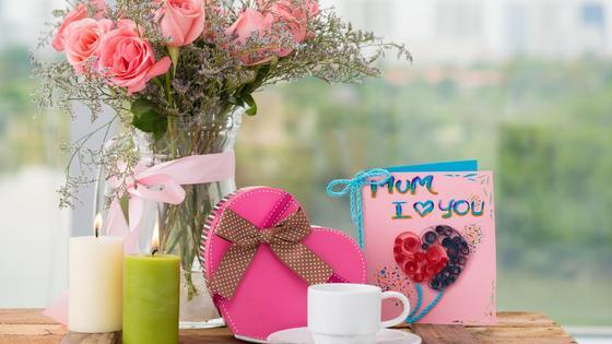 цветы в вазе, открытка, свечи, подарок и чашка