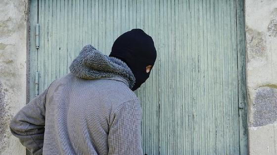 Мужчина в маске стоит возле двери