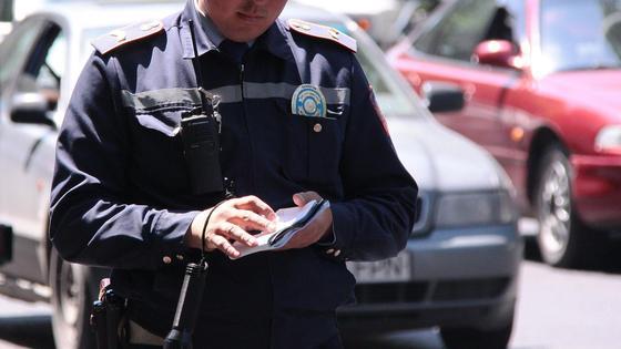 Полицейский стоит с блокнотом в руках
