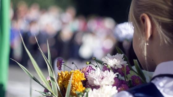 Девочка стоит на линейке с цветами