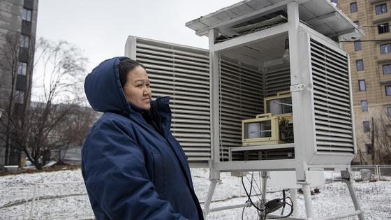 Женщина стоит около метеостанции