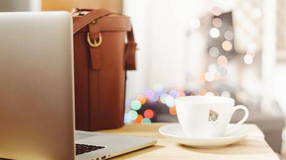 Ноутбук, чашка чая и сумка стоят на столе