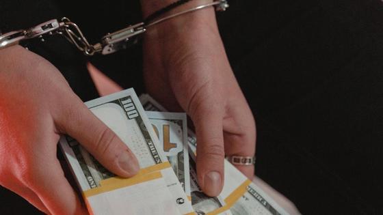 Девушка в наручниках с долларами