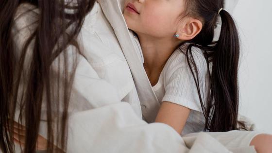 Женщину обнимает маленькая дочь
