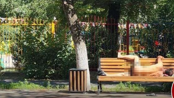 Голый мужчина на лавочке рядом с детским садом