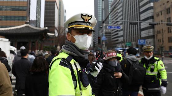 Южнокорейский полицейский держит в руках рацию