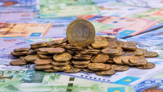 Груда монет лежит на купюрах тенге