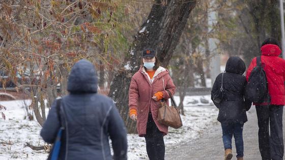 Люди в масках и теплой одежде идут по улице