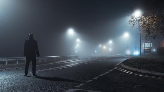 Мужчина стоит на дороге ночью
