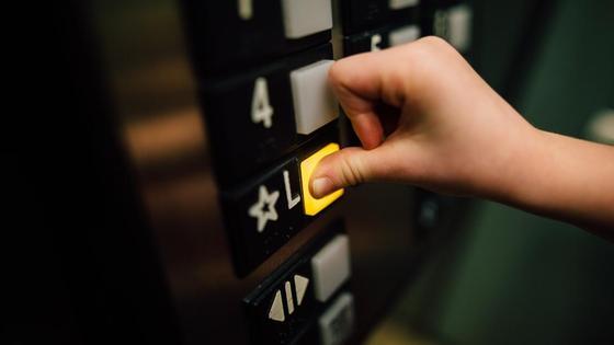 Человек нажимает пальцем на кнопку в лифте