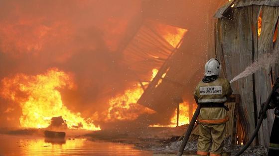 пожарный тушит полыхающее здание