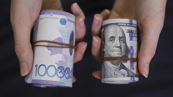 Девушка держит в руках пачку долларов и пачку тенге