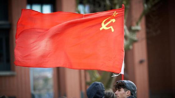 мужчин держит в руках флаг СССР