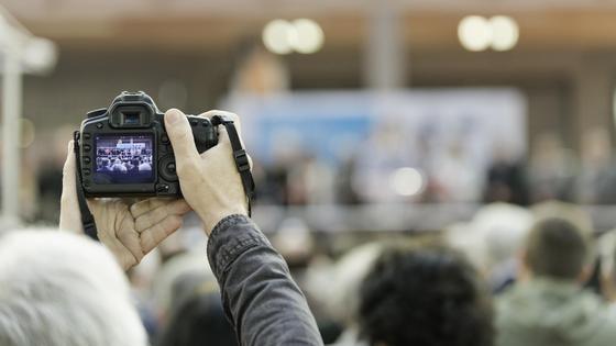 Человек в толпе держит в руках камеру