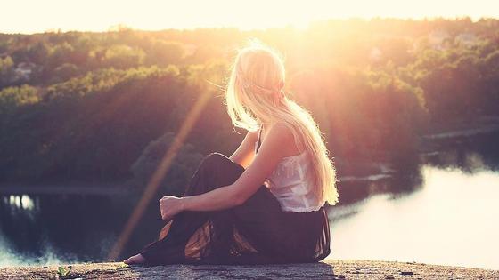 девушка сидит на фоне природы