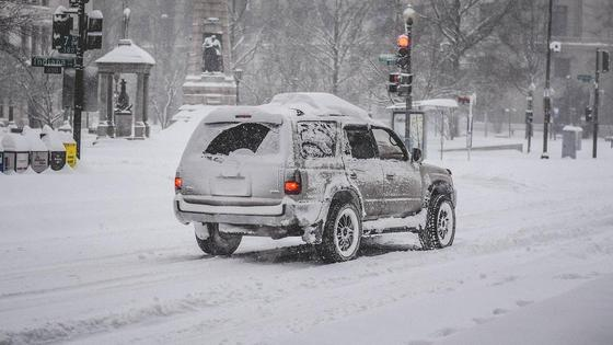 Заснеженный автомобиль едет по дороге