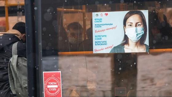 Плакат с девушкой в медмаске, размещенный на стекле автобуса