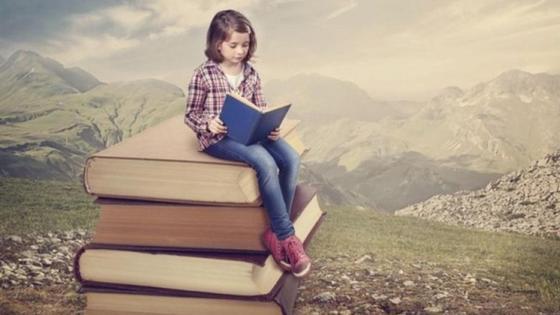 девочка сидит на стопке книг и читает