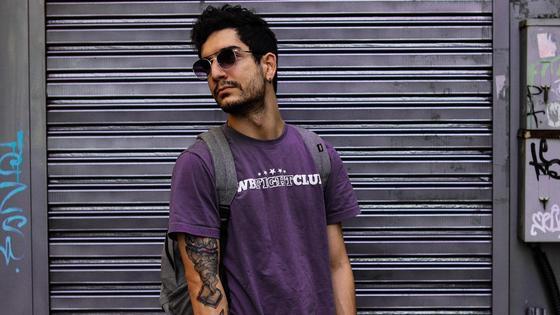 парень в фиолетовой футболке держит скейт