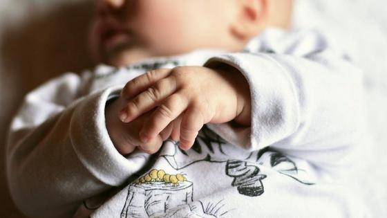 Ребенок спит, сложив ручки на животе