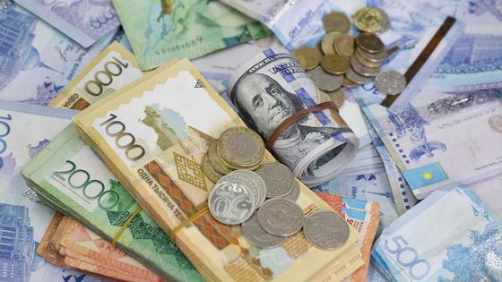 Долларовый gangster roll лежит среди тенге