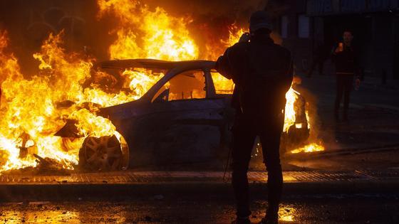 Человек стоит на фоне горящего автомобиля