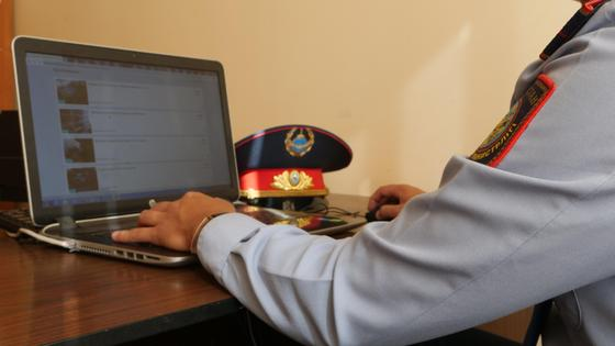 Сотрудник полиции сидит перед ноутбуком