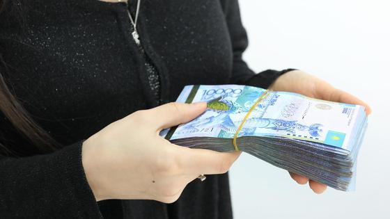 Женщина держит пачку купюр номиналом 10 тысяч тенге