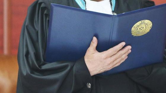 Судья держит в руках папку