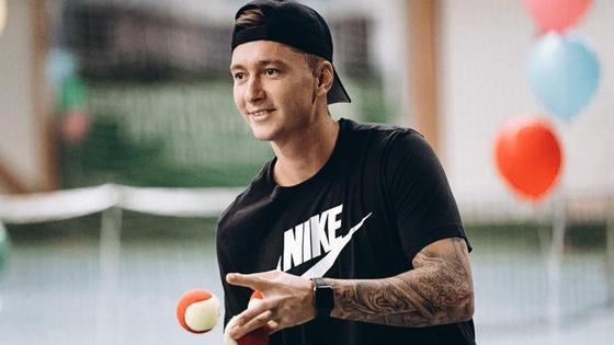 Денис Евсеев подбрасывает теннисный мяч