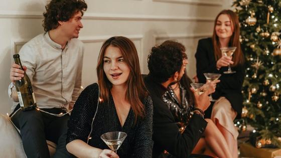 компания девушек и парней пьет шампанское возле елки