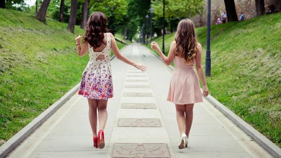 Две девушки идут по тротуару