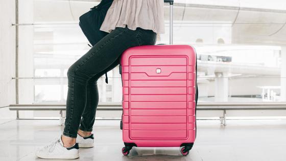 Женщина сидит на чемодане в аэропорту