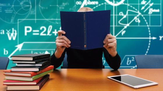Учитель сидит с книгой за столом