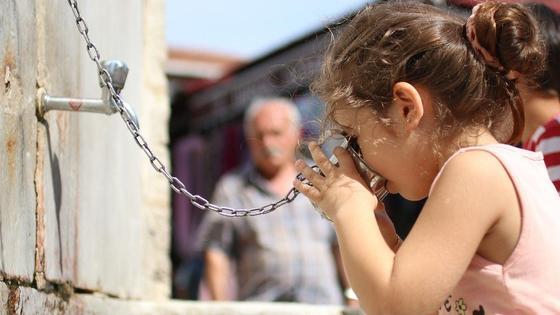 Девочка пьет воду из металлической кружки