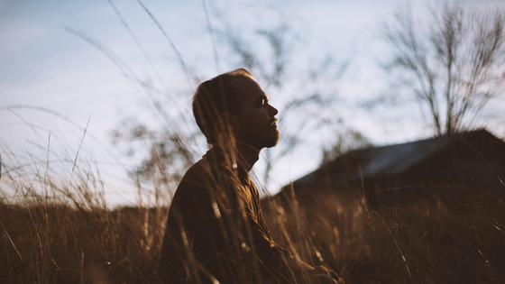 Мужчина медитирует в поле