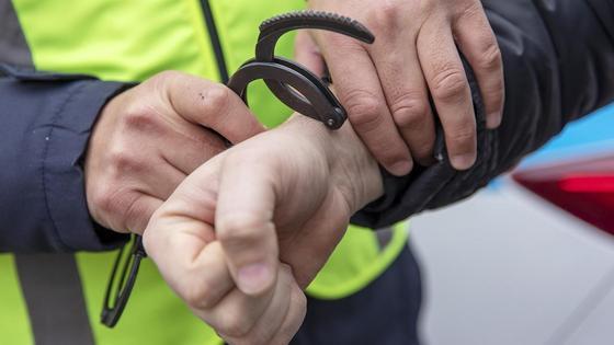 Полицейский одевает наручники на задержанного
