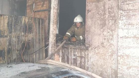 Пожарный стоит за окном в пострадавшем от пожара здании