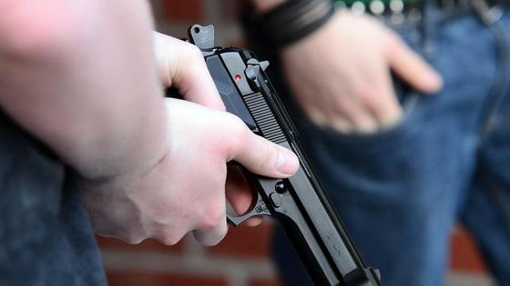 Парень держит пистолет в руке