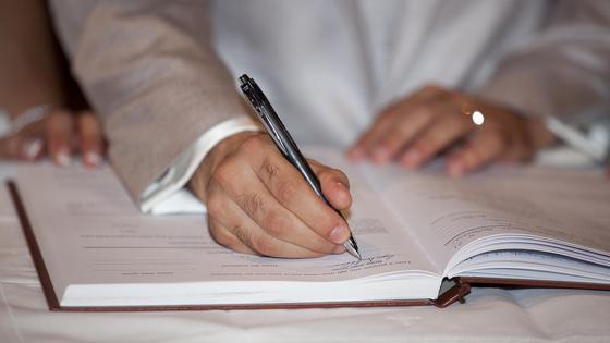 мужчина пишет ручкой в журнале