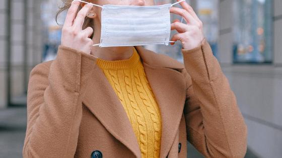 Девушка надевает медицинскую маску