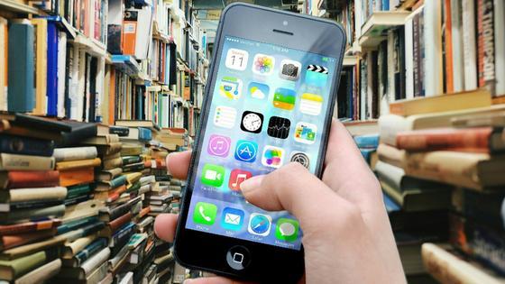 Студент держит телефон на фоне библиотеки