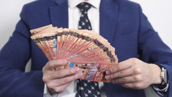 мужчина держит в руках пачку денег