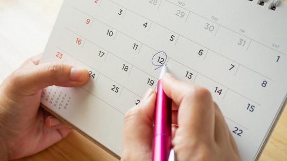 Женщина отмечает даты в календаре